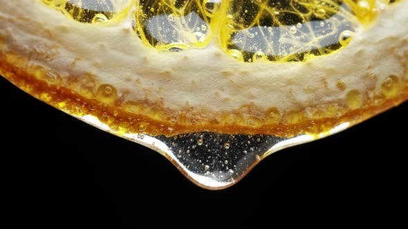 Thumbnail for Macro Texture Shot of Honey Dripping Down a Fresh Lemon Slice on White. Freshness, Citrus and Flu