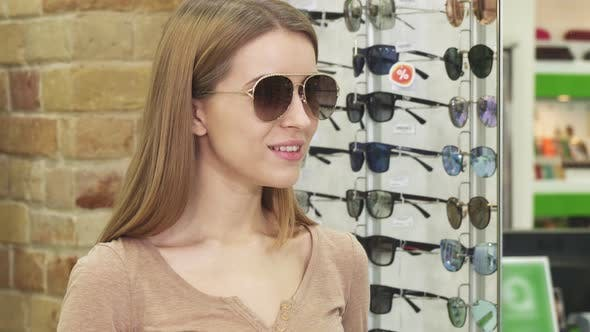 Thumbnail for Cheerful Beautiful Woman Trying Sunglasses at Optometrist Store