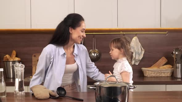 Mom and Little Daughter Dancing in the Kitchen