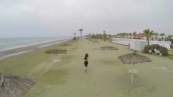 Thumbnail for Young Woman with Slim Figure Running Along Empty Beach in Cyprus, Aerial Shot