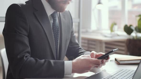 Thumbnail for Businessman Texting on Smartphone at Office Desk