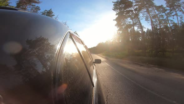 Black Automobile Riding Fast on a Country Roadway