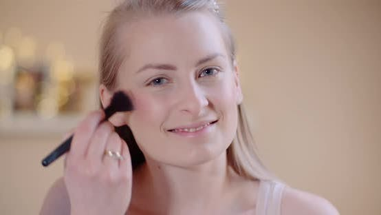Cover Image for Attractive Female Doing Makeup Applaying Powder Witha Brush