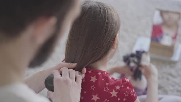 Thumbnail for Young Bearded Father Brushing the Hair of His Little Girl While the Child Combing Her Toy Sitting on