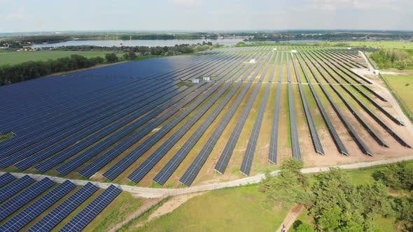 Cover Image for Aerial View on Solar Power Station in Green Field Near River at Sunny Day