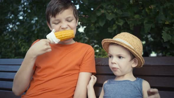 Thumbnail for Footage Two Brothers Eating Boiled Corn Sitting on Bench in Park