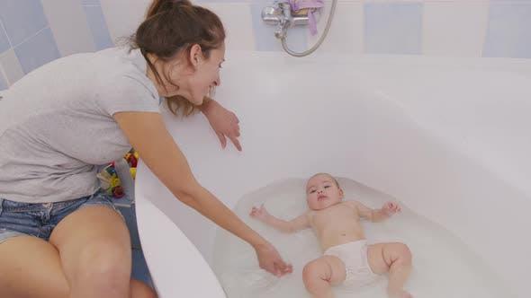 Mother Bathing Little Baby In Bathtub