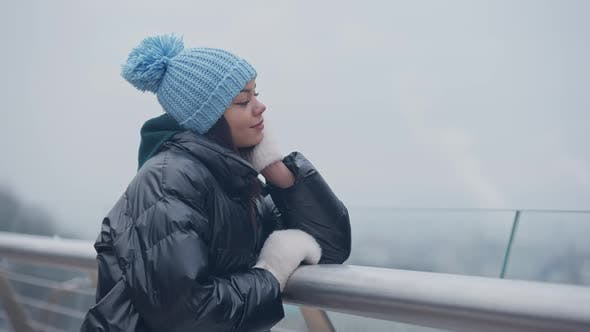 Relaxed Charming African American Woman Standing at Bridge Rails on Misty Winter Day Dreaming