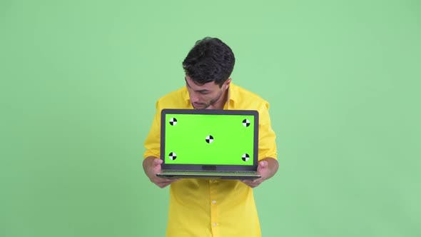 Thumbnail for Happy Young Hispanic Businessman Showing Laptop and Looking Surprised