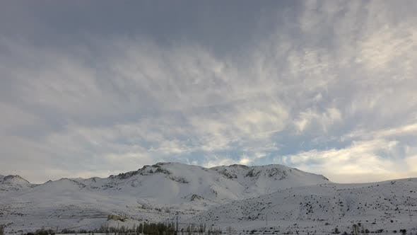 Thumbnail for Thin Cloud Layer Over Low Snowy Mountains