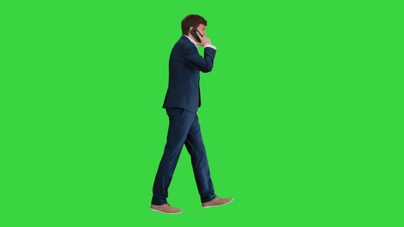 Thumbnail for Young Businessman Talking on the Phone While Walking on a Green Screen, Chroma Key.