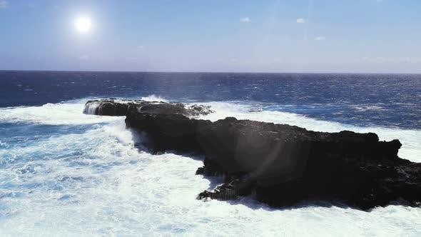 Vagues éclaboussant contre le rocher volcanique dans l'île de Rapa Nui, île de Pâques, Chili.