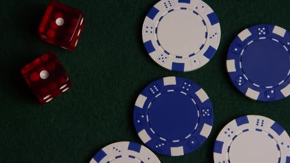 Rotating shot of poker cards and poker chips on a green felt surface - POKER 039