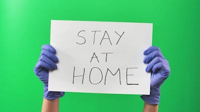 Hands Doctor Woman in Blue Gloves Holding a Sign with an Appeal To Stay at Home. Green Screen. Close