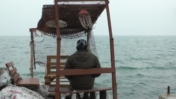 Thumbnail for Alone Man Sitting In Wooden Historical Fisherman Building And Looking Sea