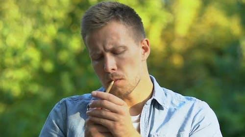 Hübscher Mann, der Zigarette anzündet und bitterer Rauch einatmet, im Freien