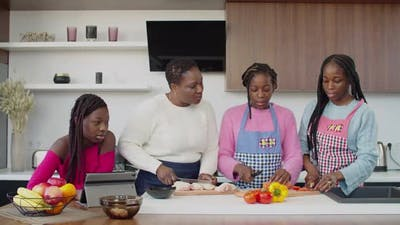 United Black Family Preparing Lunch Together in Kitchen