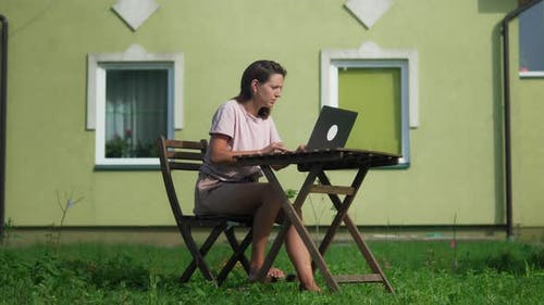 A Woman Working On Her Backyard With Her Laptop
