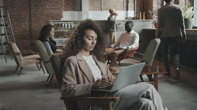 Young Businesswoman Working on Laptop in Coworking Office