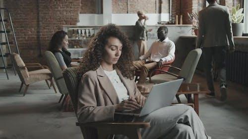Junge Geschäftsfrau arbeitet im Coworking-Office am Laptop
