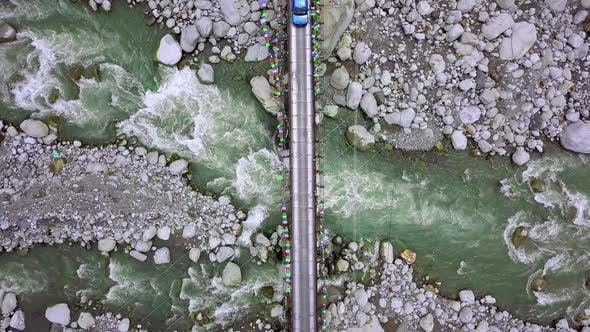 Thumbnail for A Beautiful Aerial Looking Down Shot of Bright Blue Car Crossing a Suspension Bridge