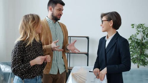 Couple of Buyers Talking To Real Estate Agent Discussing Sales Deal in Modern House