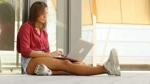 young woman sitting on the ground outdoors with a laptop