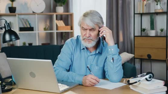 Aged Man Looking at Computer Screen while Talking on mobile