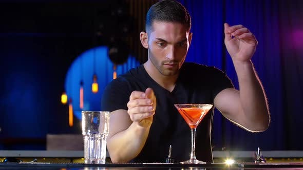 Thumbnail for Handsome Male Bartender Putting on Straw on a Cocktail Then Smiles