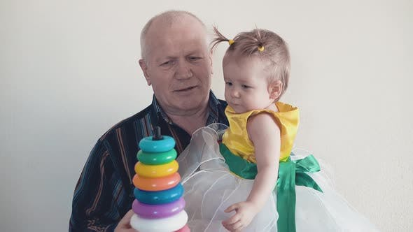 Thumbnail for Grandpa Plays with Her Granddaughter, Collects a Multi-colored Pyramid