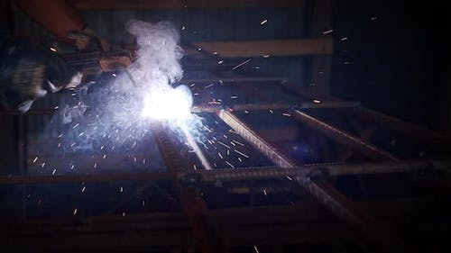 Slow Motion. Welder Welding The Worker Performs Metal Welding at the Factory or Construction Site