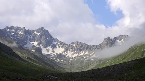 High Rocky Mountains on the Background of Glacial U Valley and Alpine Meadows