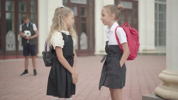 Schoolgirls Talking Before Lessons As Blurred Boy Standing with Football Ball at the Background