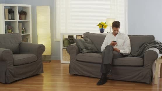 Man sitting at home using smartphone on couch
