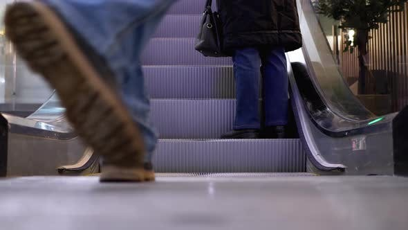 Legs of People Moving on an Escalator Lift in the Mall. Shopper's Feet on Escalator in Shopping