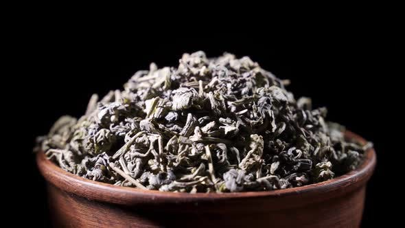 SLOW MOTION Tea Leaves Fall on a Pile of a Green Tea  Macro Shot
