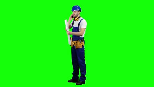 Thumbnail for Builder with a Drawing in His Hands Is Talking on the Phone. Green Screen