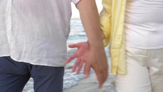 Senior couple holding hands during walk on beach