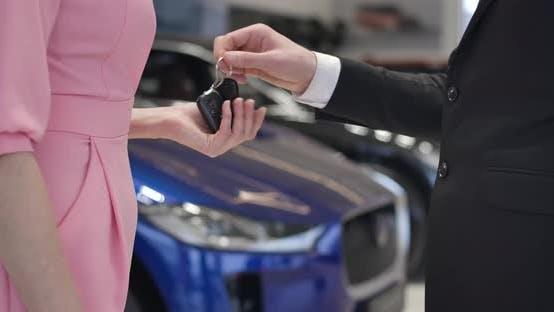 Thumbnail for Nahaufnahme des unerkennbaren Autohändlers in Anzug geben Schlüssel für weibliche kaukasische Klientin in rosa Kleid