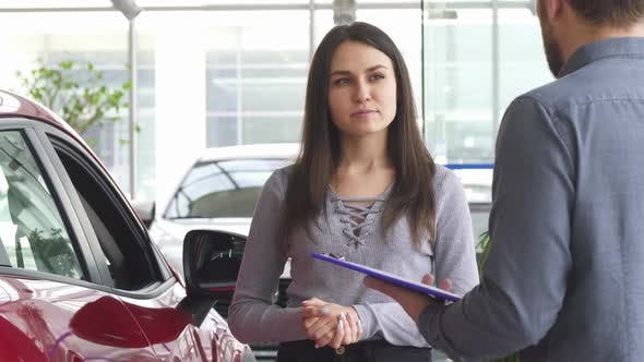 Thumbnail for Young Woman Talking to the Salesman at the Car Dealership