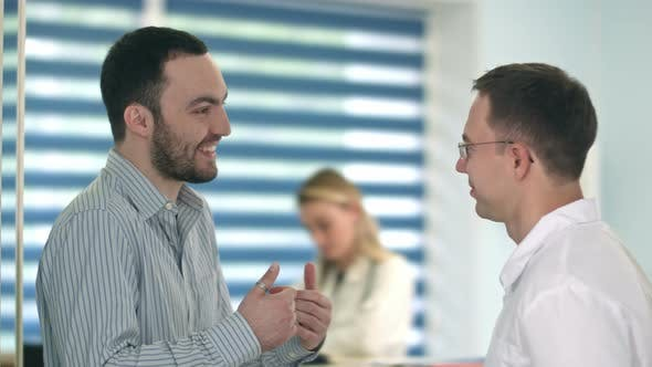 Thumbnail for Smiling Male Patient Telling Story To Male Doctor
