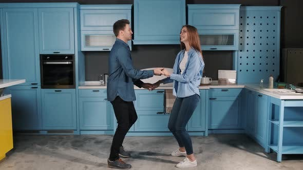 Thumbnail for Happy Young Couple Fun Dancing While Cooking in the Kitchen at Home. They Holding Their Hands