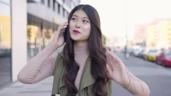 Thumbnail for Young Asian Woman Talks Smartphone Smile Street Urban Area