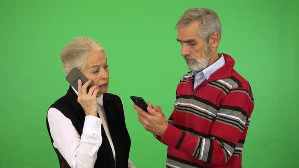 Thumbnail for An Elderly Couple, the Woman Talks on a Smartphone, the Man Works on One - Green Screen Studio