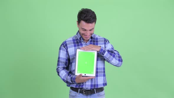 Thumbnail for Happy Young Hispanic Man Thinking While Showing Digital Tablet