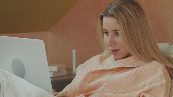 Thumbnail for Full Length Side View of Female Patient Using Laptop on Bed in Hospital
