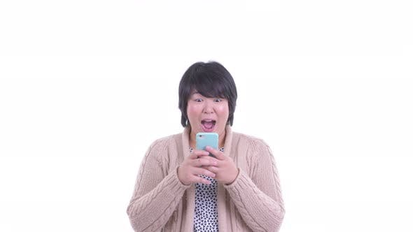 Thumbnail for Face of Happy Overweight Asian Woman Using Phone and Looking Surprised for Winter