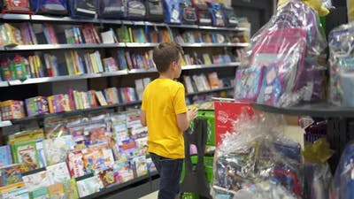 Boy choosing school supplies. Portrait of school boy shopping at supermarket