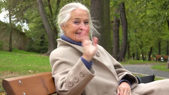 Thumbnail for An Elderly Woman Sits on a Bench in a Park and Waves at the Camera with a Smile