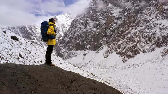 Tourist on Mountain Top. Sport and Active Life. Hiker with Backpack Standing on Top of a Mountain